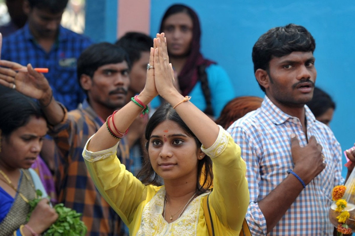 At the Chilkur Balaji Temple near Hyderabad, an Indian woman prays to Lord Balaji, known as the 'Visa God', to grant her wish to work in the US. Photo: AFP
